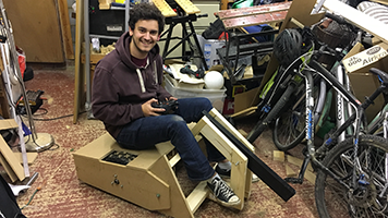 Tom sitting on the wooden prototype